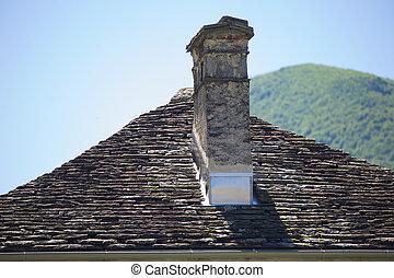 El tejado gris con chimenea de un pueblo pequeño