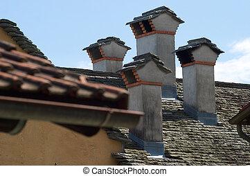 El tejado gris con chimeneas de un pueblo pequeño