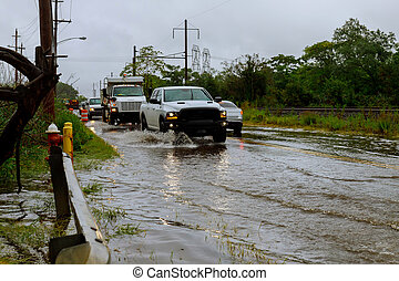 El tráfico de coches en una fuerte lluvia en una carretera inundada