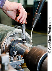 El trabajador mide sobre la máquina giratoria industrial. Industria