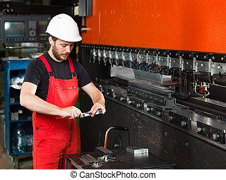 El trabajador mide un pedazo de metal