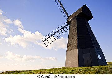 El viejo paisaje de madera de molino de viento contra el cielo azul vivo