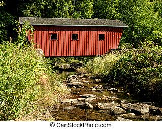 El viejo puente de madera cubierto cruzando un pequeño río