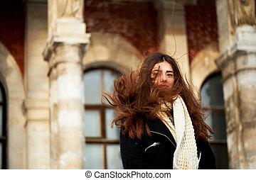 El viento en tu cabello. Una joven mirando a la cámara. Ojos largos y marrones. Estilo de vida