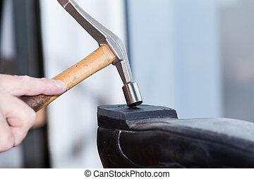 El zapatero repara un zapato