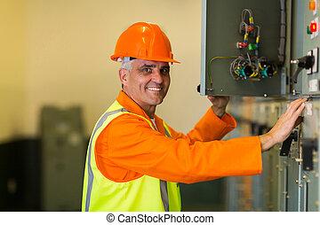 Electricista de mediana edad revisando la caja de control industrial