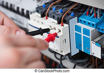 Electricista examinando la caja de fusibles con sonda multimétrica