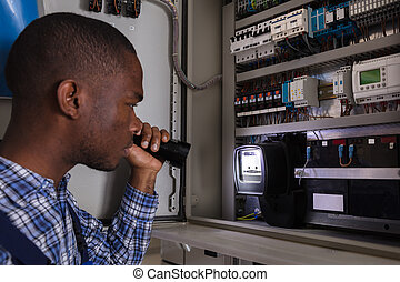 Electricista examinando un medidor eléctrico