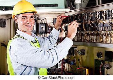 Electricista trabajando en la máquina industrial