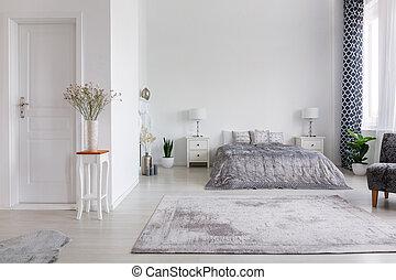 Elegante dormitorio estilo Nueva York con cama cómoda, foto real con espacio de copia en la pared blanca