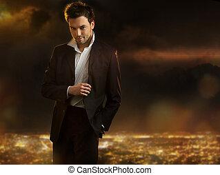 Elegante joven y guapo hombre en la ciudad nocturna