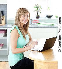 ella, computador portatil, hogar, rubio, utilizar, sonriente, cámara, cocina, mujer, encantado