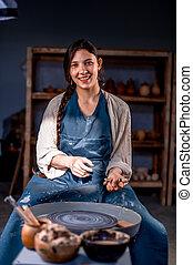 ella, maestro, mientras, sentado, artesano, simpático, llevando, elaboración, delantal, earthenware., chair., posar