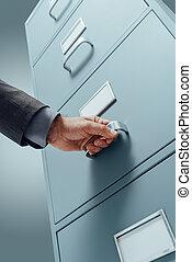 Empleado de oficina buscando archivos en el archivador