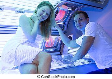 Empleado en un asesor de solárium o cliente en la cama de bronceado