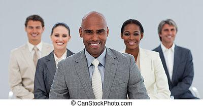 Empresario étnico carismático con su equipo sonriendo