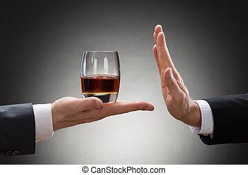 Empresario rechazando whisky ofrecido por empresarios