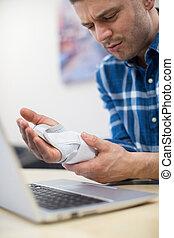 Empresario usando portátiles que sufren de lesiones repetitivas.