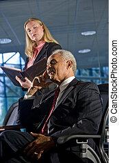 Empresario y asistente femenina en una reunión de la sala de juntas