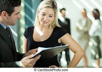 Empresario y mujer de negocios mirando el documento