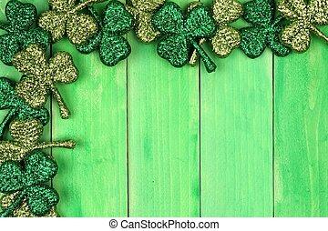 En la esquina del día de San Patricio, la frontera de brillantina brilla sobre un fondo de madera verde