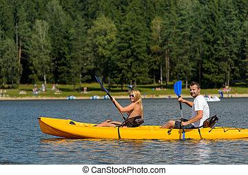 En una pareja joven del estanque sentada en kayak