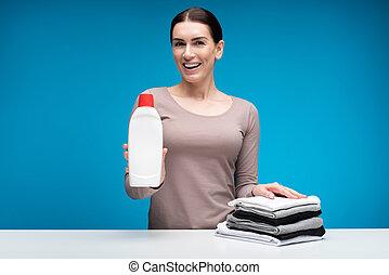 Encantadora mujer mostrando ropa después de usar detergente