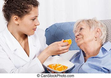 Enfermera alimentando a una anciana