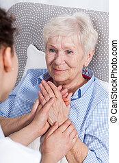 Enfermera consolando a anciana