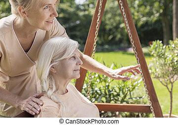 Enfermera cuidando de un veterano en un jardín