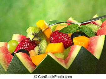 Ensalada de fruta fresca (Fresa, kiwi, mango, uva) en cuenco de melón con kiwi y mango en tenedor y una hoja de menta como guarnición en frente de fondo verde (Céntrate selectivo, en la fruta en el tenedor