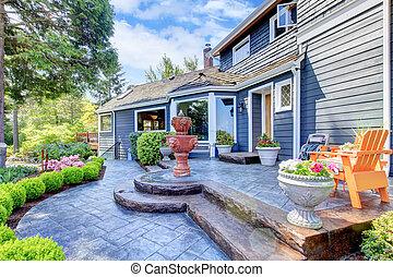 Entrada de casa azul con fuente y lindo patio.