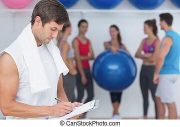 Entrenador escribiendo en el portapapeles con clase de fitness en el fondo