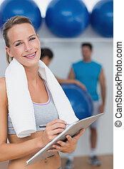 Entrenador sosteniendo portapapeles con clase de fitness en el fondo