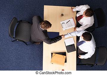Entrevista de trabajo, tres hombres de negocios reuniéndose con uno
