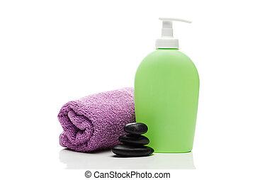Envases cosméticos, toallas y piedras de spa negras aisladas en blanco