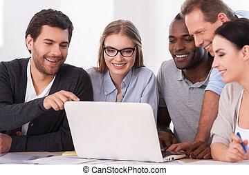 Equipo creativo en el trabajo. Un grupo de empresarios con ropa informal sentados juntos en la mesa y discutiendo algo mientras miran el portátil