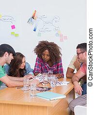 Equipo creativo hablando sobre las hojas de contacto en la reunión