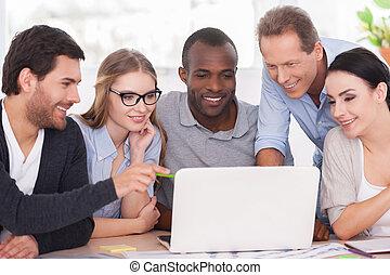 Equipo creativo trabajando en proyecto. Un grupo de empresarios con ropa informal sentados juntos en la mesa y mirando el portátil