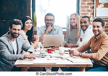 Equipo creativo. Un grupo de seis jóvenes alegres mirando a la cámara con una sonrisa mientras se sientan en la mesa en la oficina