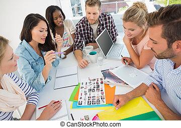 Equipo de diseño joven revisando las hojas de contacto en una reunión