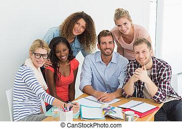 Equipo de felices jóvenes diseñadores teniendo una reunión sonriendo a cámara en oficina creativa
