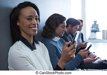 Equipo de gente de negocios usando teléfono móvil