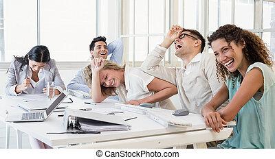 Equipo de negocios casual riendo durante la reunión