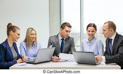Equipo de negocios con portátil teniendo una discusión