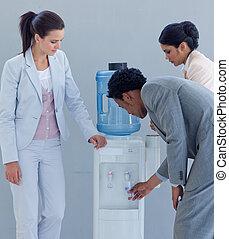 Equipo de negocios con un refrigerador de agua en la oficina