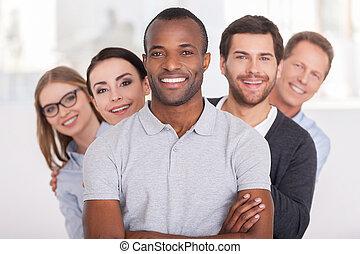 Equipo de negocios confiado. Un joven africano alegre con brazos cruzados y sonriendo mientras un grupo de gente detrás de él en fila y mirando a la cámara
