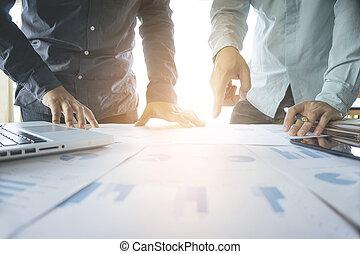 Equipo de negocios dos colegas discutiendo nuevos datos del plan financiero en la mesa de oficina con portátil y tableta digital.