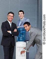 Equipo de negocios multiétnico en el refrigerador de agua