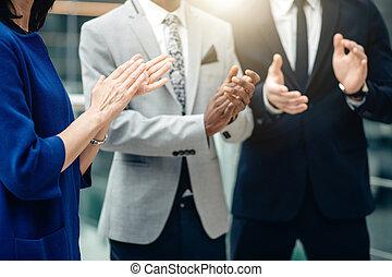 Equipo de negocios multiracial aplaudiendo a sí mismos por un gran trabajo hecho